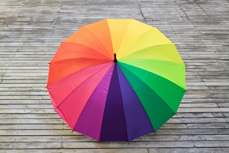 Multi-colored umbrella on wood  background  photo