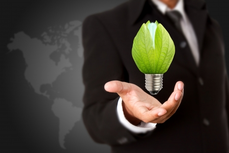 save electricity: Businessman holding green light bulb, concept of saving energy