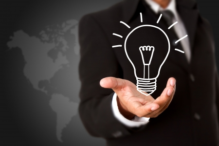 Light bulb in business hand with world map background photo