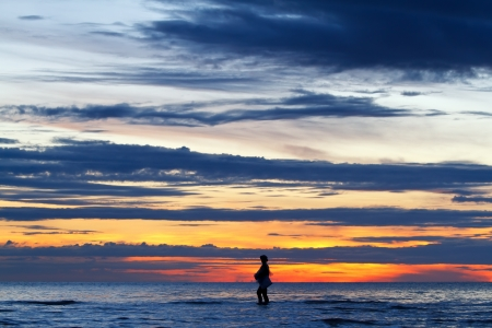 Silhouette image of fisherman walking in the huahin sea, Thailand photo