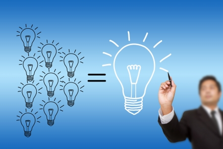 Businessman drawing light bulb photo