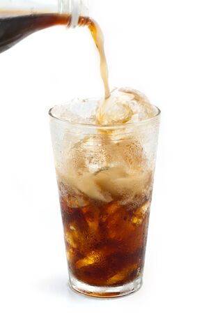 A Bottle of cola soda pouring into a glass filled with ice cubes over a white background