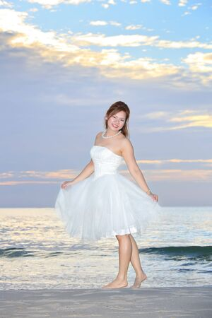asian woman bride in her wedding dress in sunshine on a beautiful  beach photo