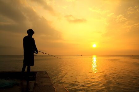Fisherman fishes on the sea. Silhouette at sunrise photo