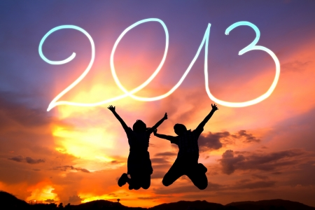 happy new year 2013. young couple  jumping happy 2013 by flashlight in the air on the beach before sunrise photo