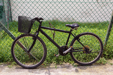 Black bicycle leaning against black iron fence  photo