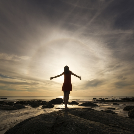 fits in: Happy celebrating winning success woman at sunset or sunrise standing on a beach Stock Photo