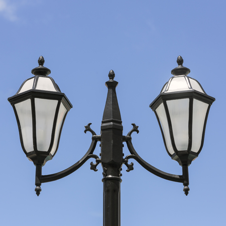 Victorian lamp post standing on blue sky photo
