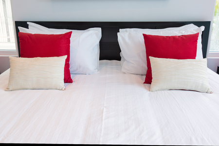 red pillows: White and red pillows on a bed Comfortable soft pillows on the bed