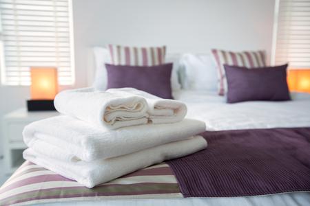 hospedaje: Toallas de baño en la cama de la habitación del hotel Foto de archivo