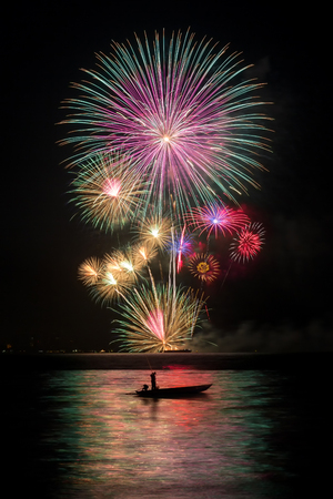 fires artificial: Fireworks with a fishing boat  in the sea
