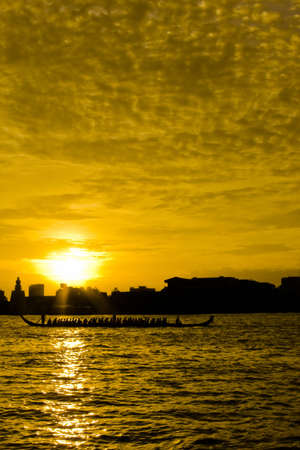 Ancient royal thai paddling boat on Chao Phraya river in a golden twilight Stock Photo