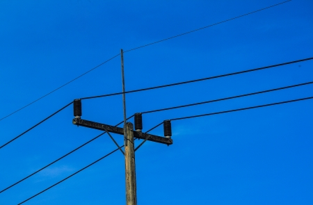 Silhouette of Electricity post at sunset with blue sky photo