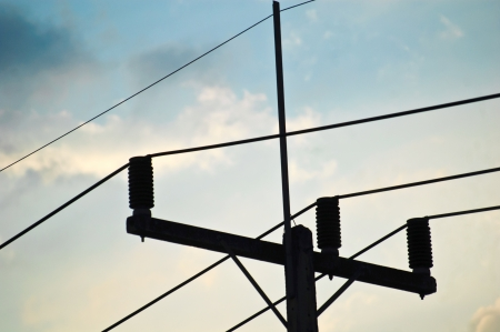 Silhouette of Electricity post at sunset with blue sky