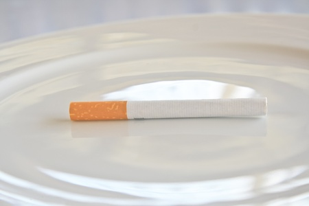 harm: Cigarette on plate  Stock Photo
