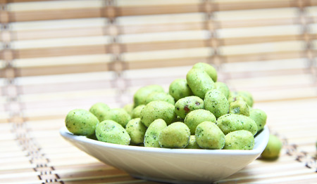 Wasabi coated peanuts on wooden. photo