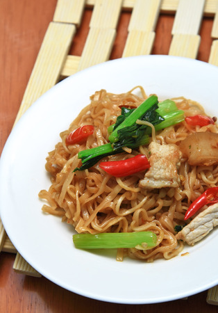 fried spicy noodles with pork and vegetables in white dish  photo