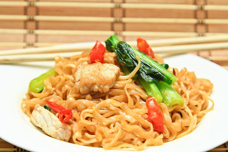 fried spicy noodles with pork and vegetables in white dish