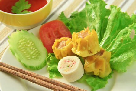 Dim sum in white dish  near Chili sauce and Vegetables. Stock Photo