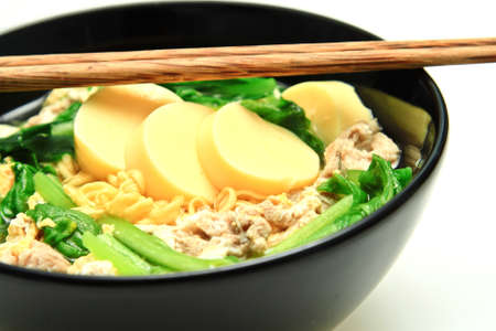 Noodle in black bowl with vegetables. photo