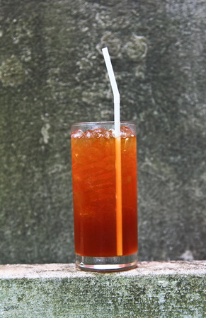 thirst quenching: Glass of ice tea on gray background.