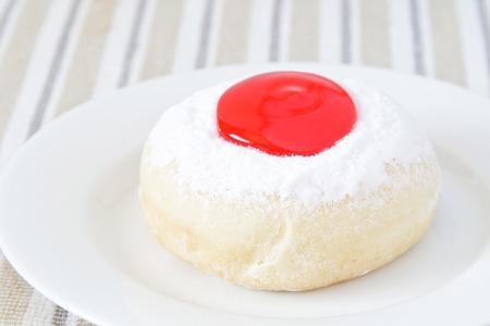 Donut mit Erdbeer-Marmelade auf weißem Teller