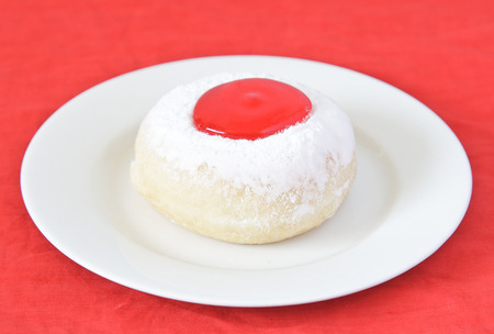 judaical: Donut with strawberry jam on white dish. Stock Photo