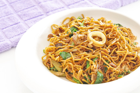 mee pok: chinese stir fried noodles in white dish.