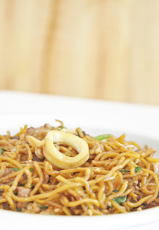 yi mein: chinese stir fried noodles in white dish.