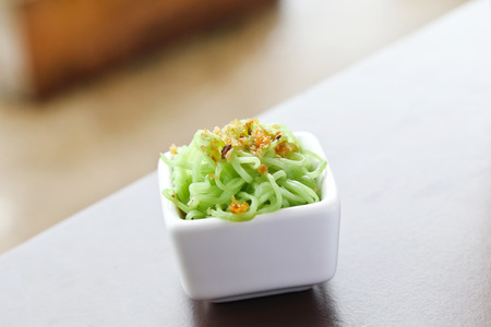 food staple: green noodle with Fried garlic in white cup.