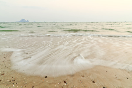 ao: Beach wave and footsteps at sunset time, Ao Nang Krabi in Thailand. Stock Photo