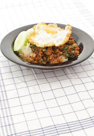 Thai stir-fried chicken and basil served with rice and fried egg photo