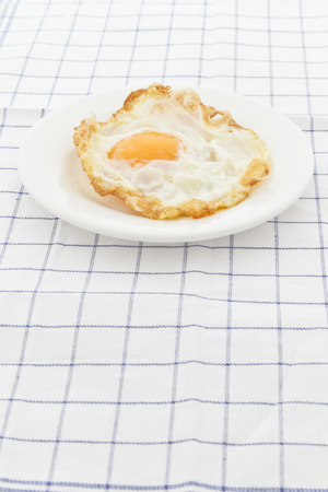 Fried egg on white plate. Stock Photo