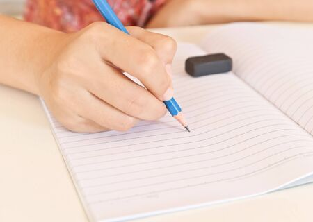 entries: womans hand writing entries in a notebook Stock Photo