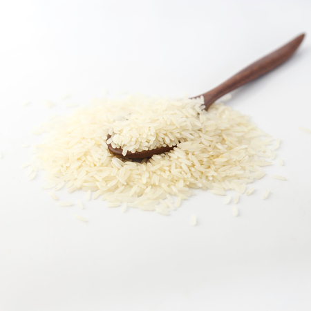 Rice in a wooden spoon on white background.