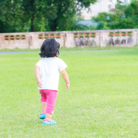 Baby girl playing in the green grass.