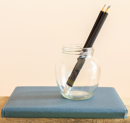 Pencil in glass bottle on notebook, Education Concept.