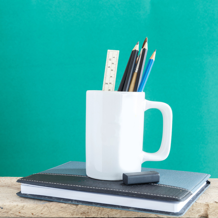 Educational Equipment on the student desk and the chalkboard background. Education Concept.