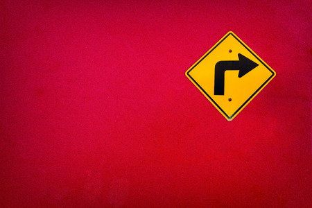 roadwork: Old Yellow traffic sign Turn right on red wall texture Stock Photo