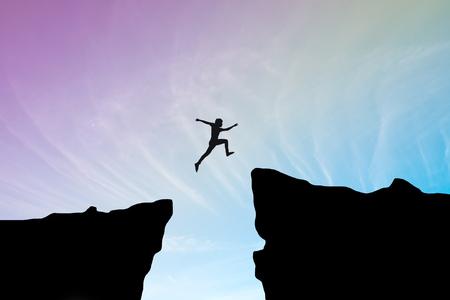 일몰 배경, 절벽을 통해 점프 hill.man 사이의 격차를 통해 점프 남자 비즈니스 컨셉 아이디어 스톡 콘텐츠