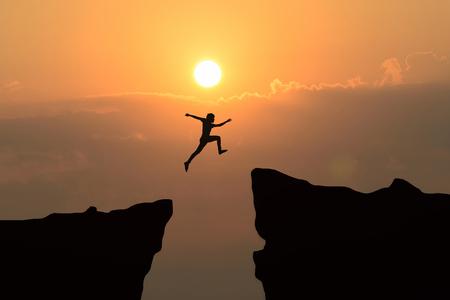Człowiek przeskakuje przez szczelinę między hill.man skoków nad urwisko na tle zachodu słońca, koncepcji koncepcji firmy