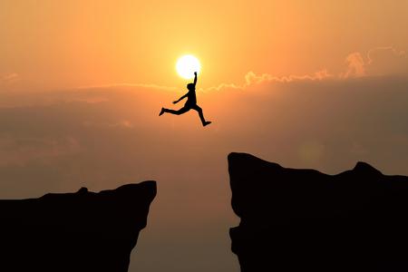 El hombre salta por el hueco entre el salto hill.man sobre el acantilado en el fondo la puesta del sol, el concepto de negocios idea Foto de archivo - 87158985