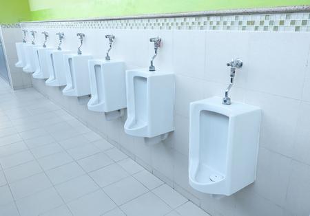 Closeup white urinals in mens bathroom, design of white ceramic urinals for men