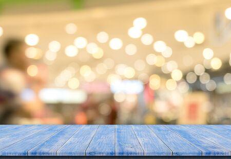 Bokehachtergrond met lege blauwe houten dektafel voor weergave van productmontage Stockfoto