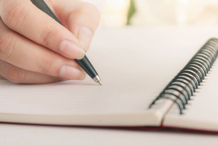Woman hand with pen writing on notebook. Blank copy space.