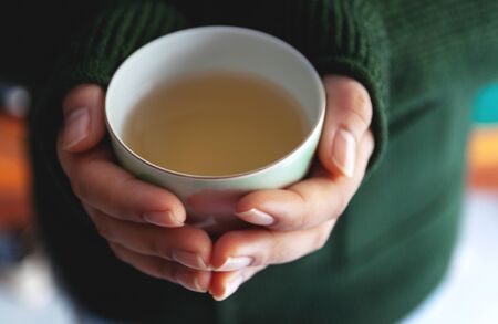 Selective focus and Soft focus / Woman hands holding hot cup of coffee or tea, With a winter 免版税图像