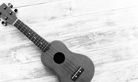 The black and white ukulele on the white wood table background, Blank copy space. Music concept