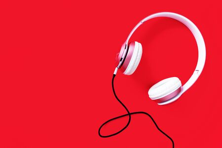 Pink headphone and black cable on pastel color red background. Music concept. Blank copy space