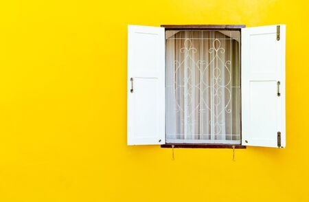 The white wooden window was opened, where the windows were on the concrete walls of yellow. with blank copy space. 免版税图像
