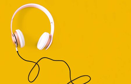 Pink headphone and black cable on pastel color yellow background. Music concept. Blank copy space